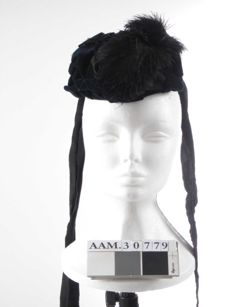 Liten hatt som dekker bakhodet. Pyntet med legg, sløyfer og fjær. Lange knytebånd.