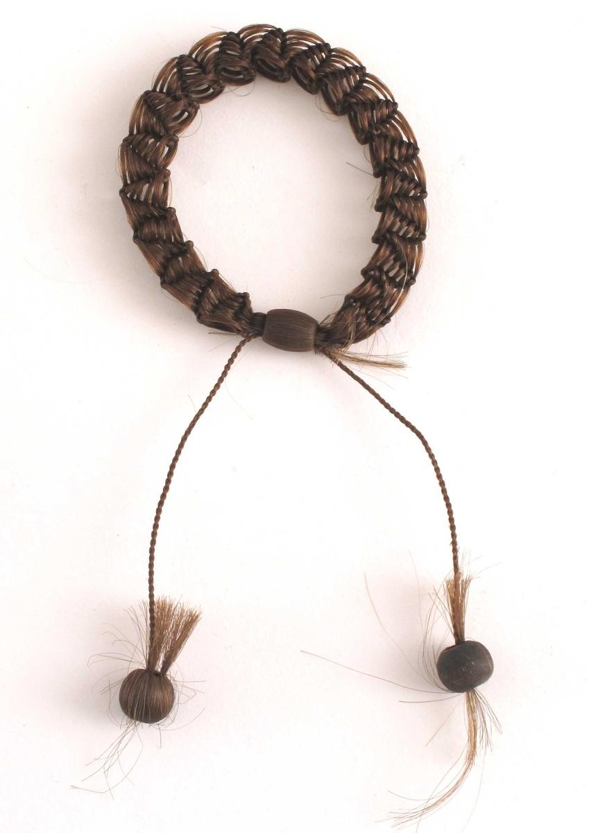 En liten ring, på størrelse med et armbånd, flettet av menneskehår-