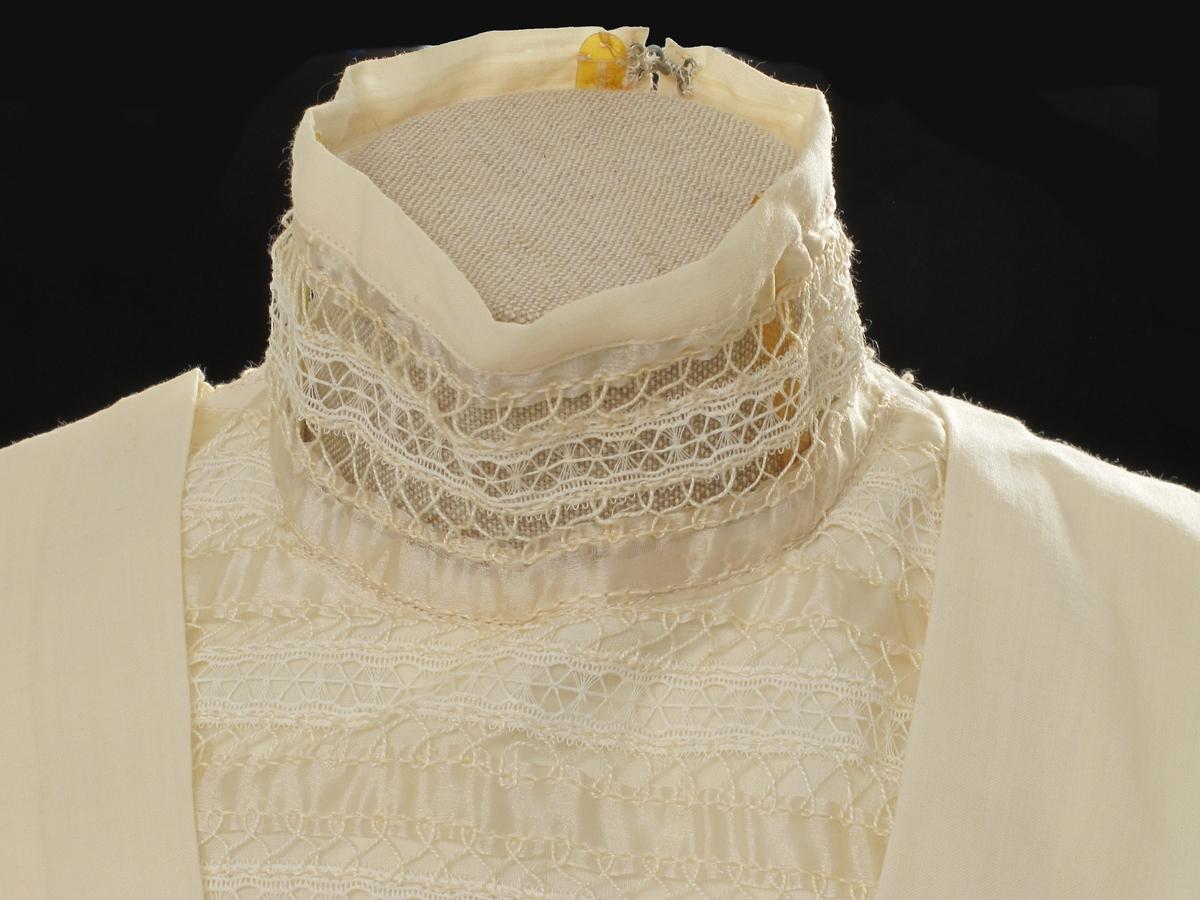 V-formet blondefelt (= sammensatt av silkebånd festet/brodert til kniplingbånd) fra hals til liv foran og bak. Ullstoffet lagt i legg i samme v-fasong på hver side av blondefeltet. Høy hals. Puffermer med blondekappe utenpå. Fra albuen smale ermer i blondestoff. I livlinje midt bak en krok til å hekte skjørtet på. Lukking med trykknapper og hekter. Gule plastspiler holder halsen oppe.
