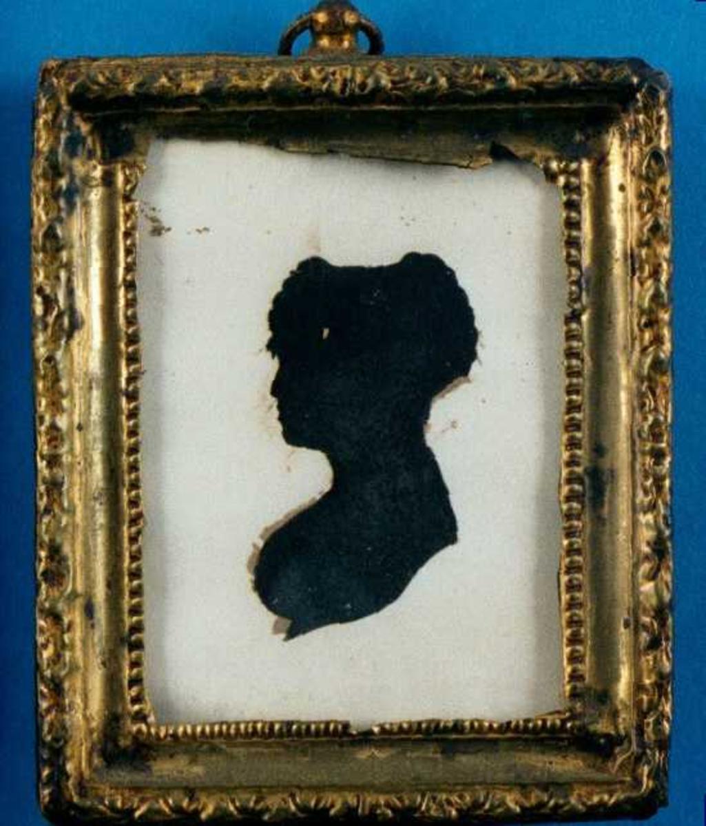 Portrett av ung kvinne. Silhouett. Profil venstre, rund barm krøllet hår over pannen, stor flat chignon (flettet?), nedskåret bue over isse