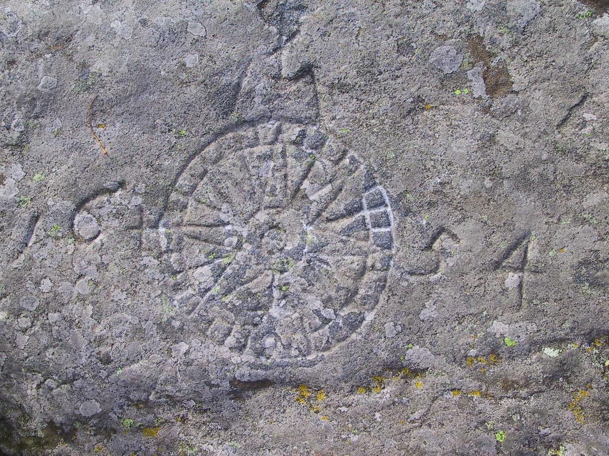 Merdø, Vestre Valen. Kompassrose innhogd i fjellet, med årstallet 1654.