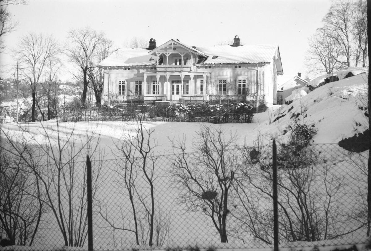 Langsæ gård, våningshuset sett fra Parkveien. Vinter og snø.  Nettinggjerde i forgrunnene.