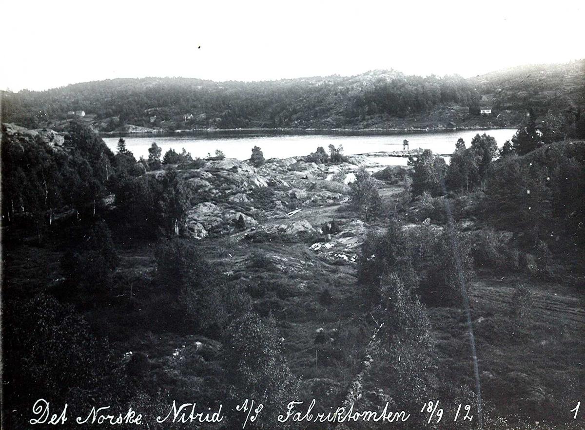"""""""18/09-1912"""" Nitriden. Tomt for fabrikkanlegget. Omformerstasjon og ovnshus. På skjæret sees fyrlykt nr. 612 i Norsk Fyrliste, bygget 1894 og flyttet til Friisøy i 1929. Tromøysund og Tromøy i bakgrunnen. Bildet er tatt fra høydebassenget."""