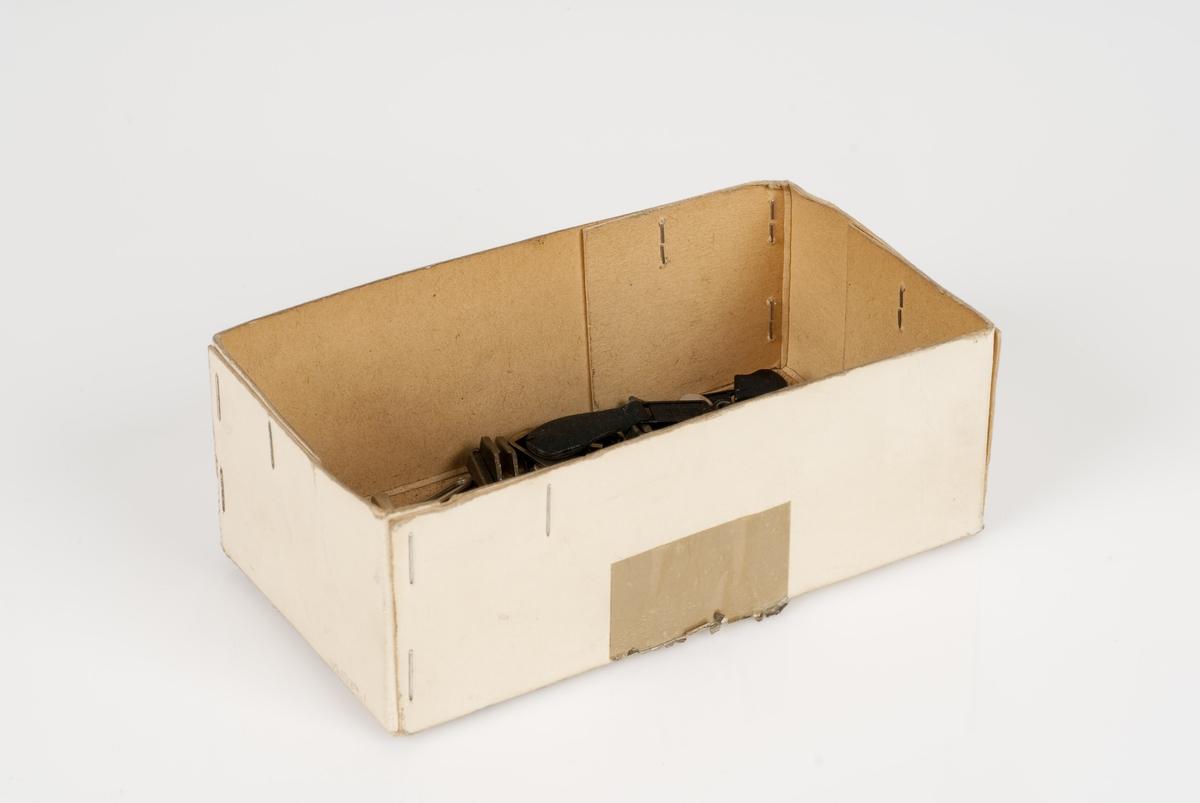 Forskjellige glidere (til glidelås) av metall i en pappeske.