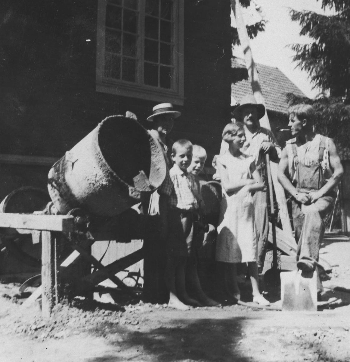 Tre voksne og tre barn ved en sementblander.Bildet er tatt foran kjemi- eller fabrikkbygning.