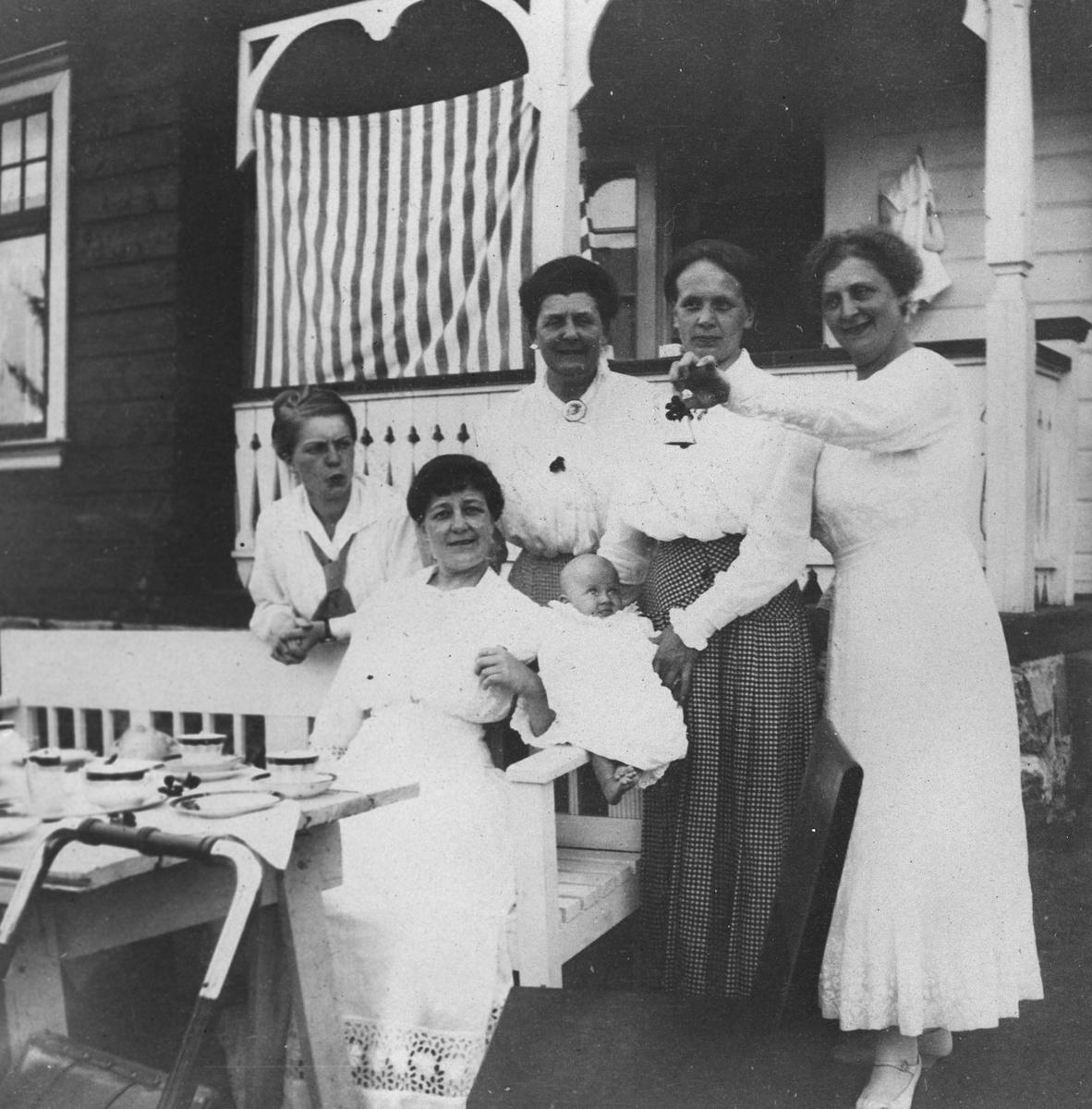 Fem damer med et lite barn foran landstedet.