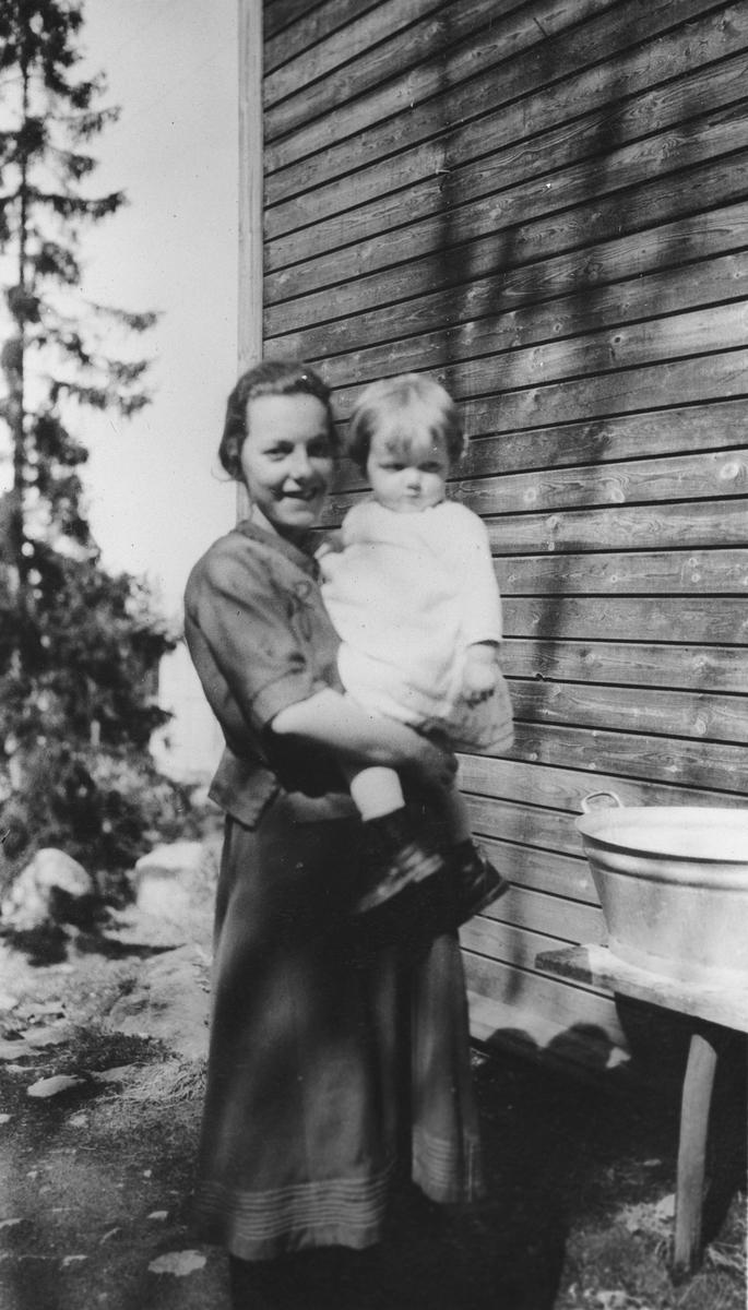 Kvinne med barn på armen ved en vaskebalje.