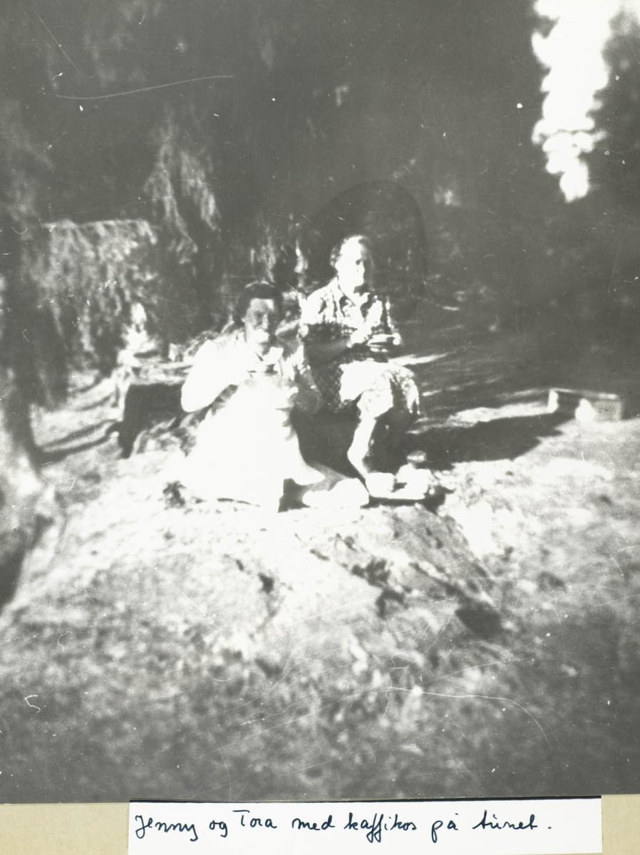 To damer sittende ute i skogen, drikker kaffe