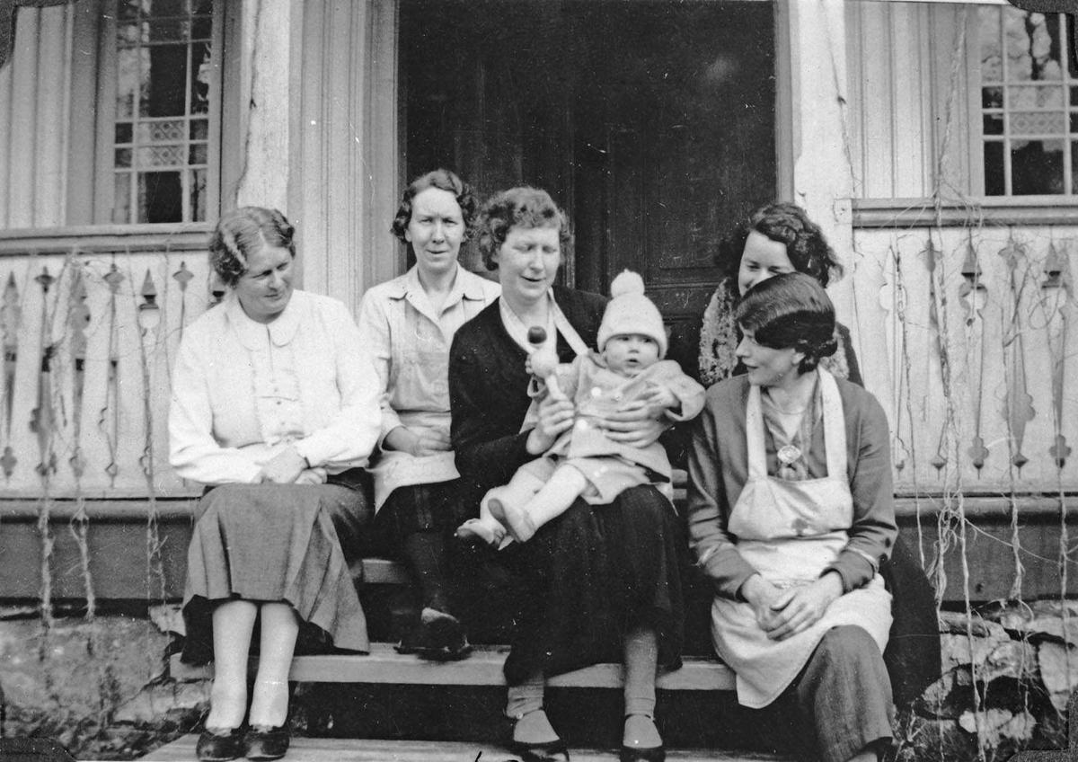 En gruppe som sitter på trappa på Baarlid gård.