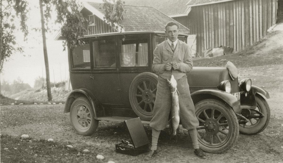 Mann med fisk står inntil bil på gårdsplass. Portabel grammofon.