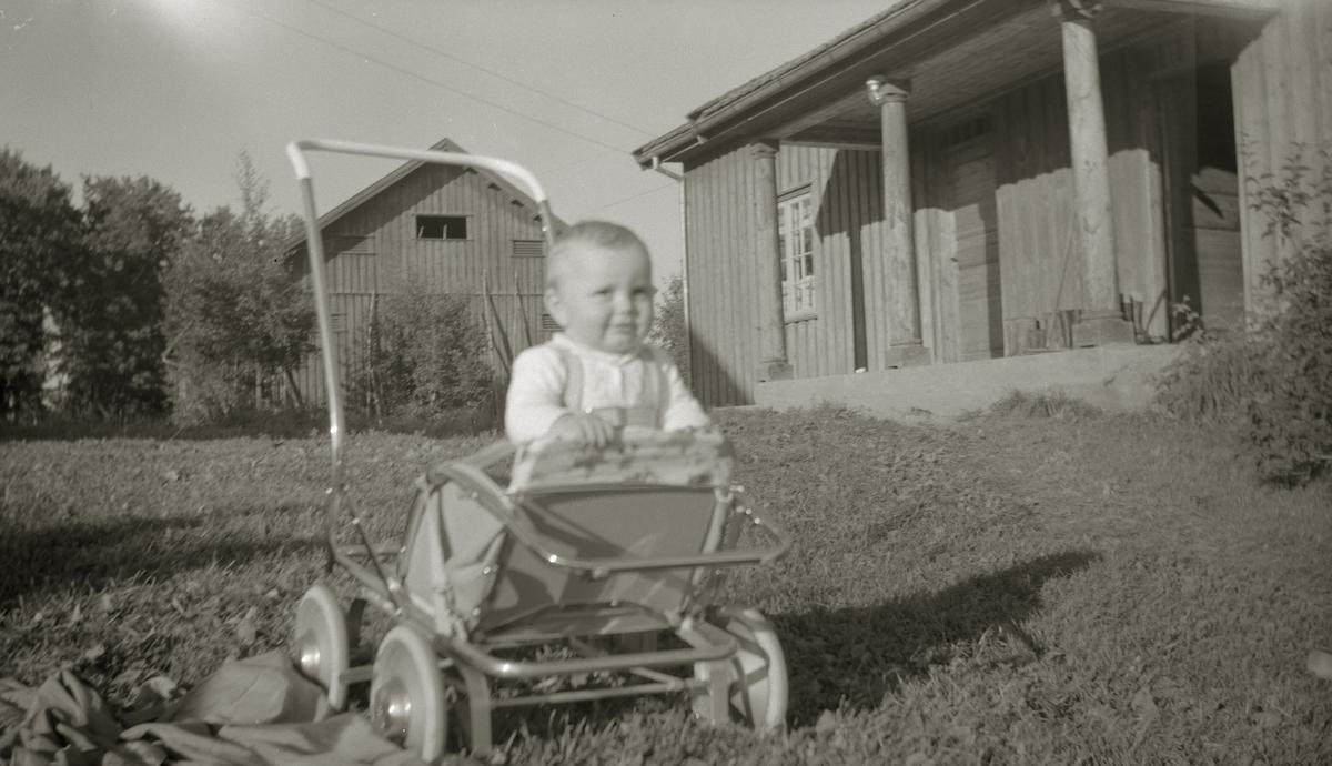 Lite barn i barnevogn/trille foran veslebygningen på Frogner gård, Ullensaker.