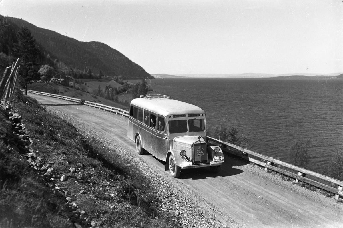 Buss av merket Mercedes med dieselmotor. I rute mellom Eidsvoll og Skreia. Bilde fra Feiring. Buss-Olsen eide bussen. 15.02.2013: Den første Mercedes bussen som Buss-Olsen (min bestefar) trafikkerte på strekningen Eidsvoll - Skreia. Dette chassiet kjøpte Buss-Olsen av Bertel O. Steen på Frognerutstillingen sommeren i 1935. Den  ble umiddelbart kjørt til Fosserud & Nygård Karosseriverksted på Styri i Edsvoll (senere Sigurd Jensen Karosseriverksted) og kom i rute i 1936. Denne ble byttet ut i 1937 med en større buss, som var avdelt med røkesalong bakerst. Jomfruturen var påskeaften 1937. Skrevet av: Hans Fredrik Hansen