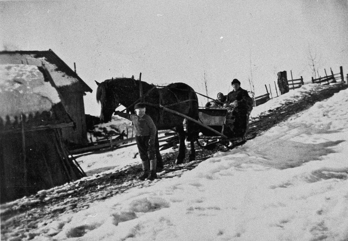 Mann, 2 barn, hest og slede vinterstid.