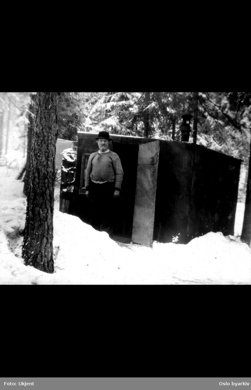 Provisorisk hytte i Abildsøskogen, mann med hatt foran døra