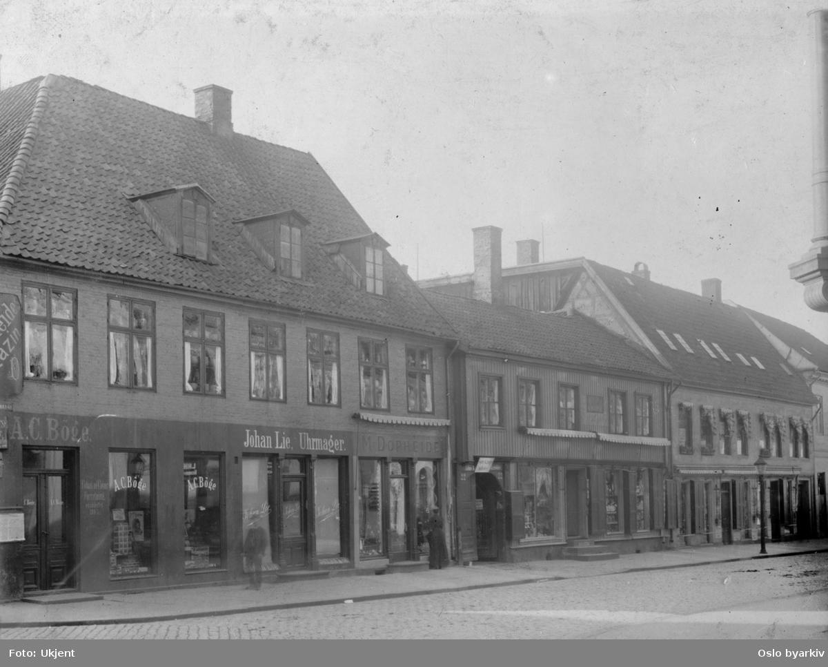 Gatemiljø med butikker. Johan Lie, Uhrmager, Storgata 16. Stadsingeniøren - Fotografier af Kristiania (albumtittel). Ca 1892, basert på øvrige daterte bilder i samme album.