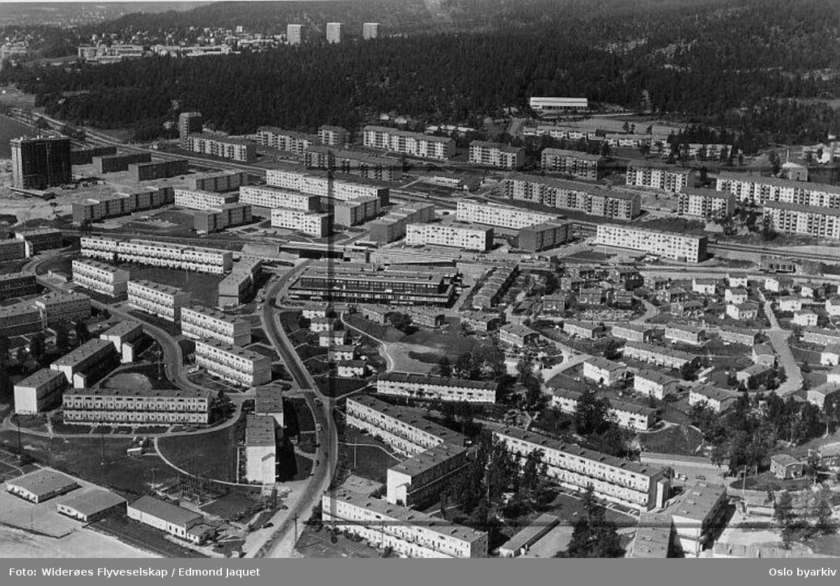 Trondheimsveien, Linderudsletta, Sletteløkka, Veitvetveien, Rådyrveien, Beverveien, Grevlingveien, Veitvetsvingen. Grorudbanens trase. Selvaagbyggs rekkehus og blokker. Til venstre for transformatorstasjon ligger Veitvet skole. (Flyfoto)