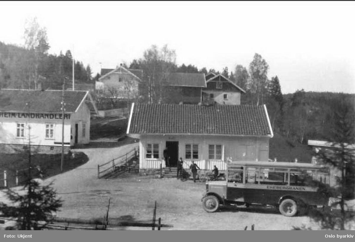 """En av Ekebergbanens busser C-4054 (1.) ved Godheim landhandleri (til venstre) og """"Se Op Hvilestue"""" i Enebakkveien. Endeholdeplass for ruta Sæter- Godheim."""