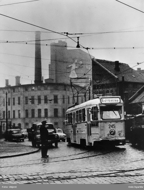 Oslo Sporveier. Trikk motorvogn 245 type Høka MBO linje 6 før svingen inn i Brugata, ved Vognmannsgata. Holters lysfabrikk i bakgrunnen.