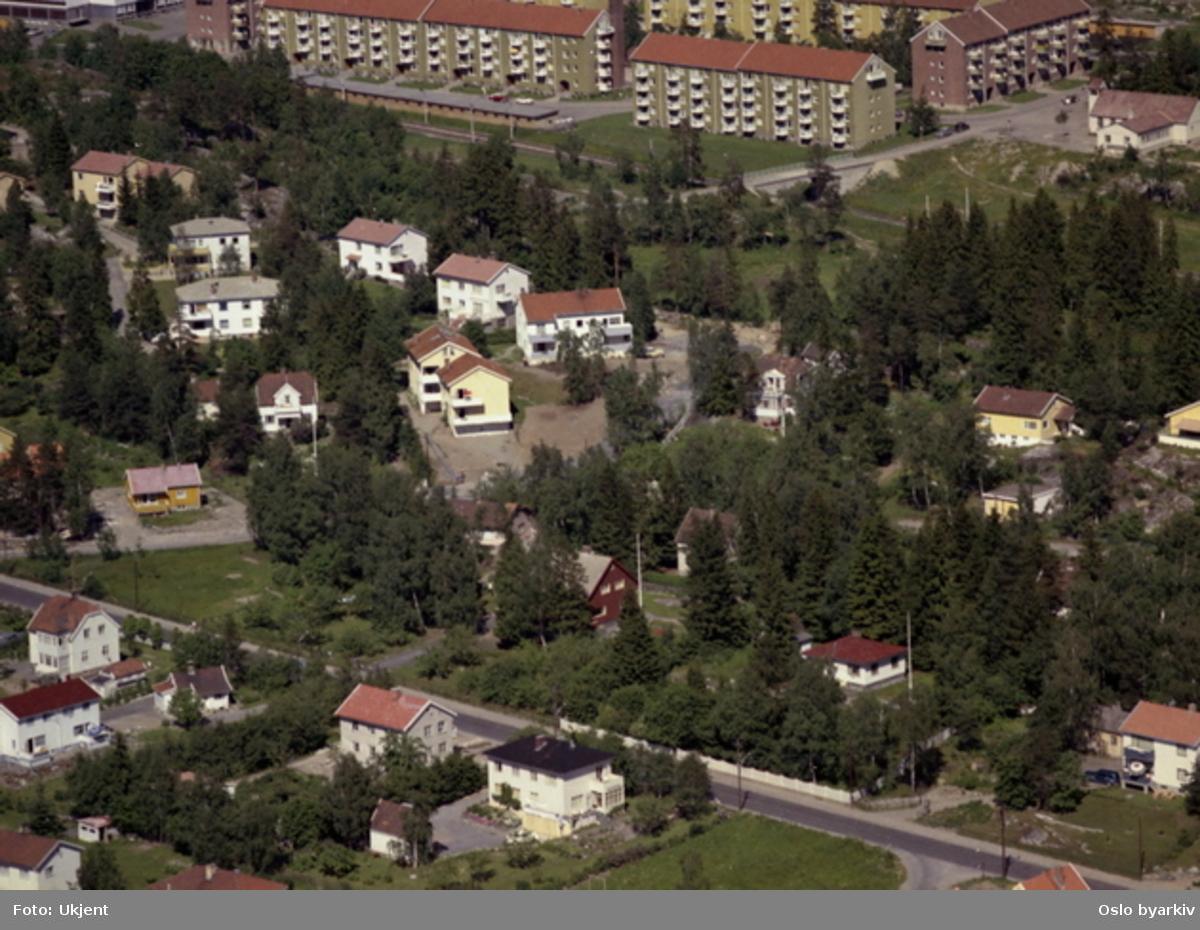 Skiferveien og Hellinga (blokker) bakerst. Lambertseter kirke bak til høyre. Bro over t-banen til Hellinga. Oberst Rodes vei og Kaptein Oppegaards vei i forgrunnen. (Flyfoto)