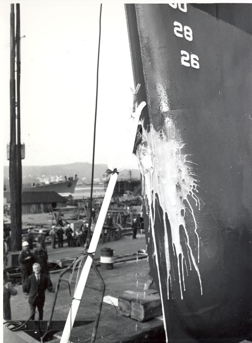 "Oslo-kl.- fregatt KNM ""Trondheim"", dåp og stabelavløpning, 4. sept. 1964. Champagneflasken knuses mot skipssiden."