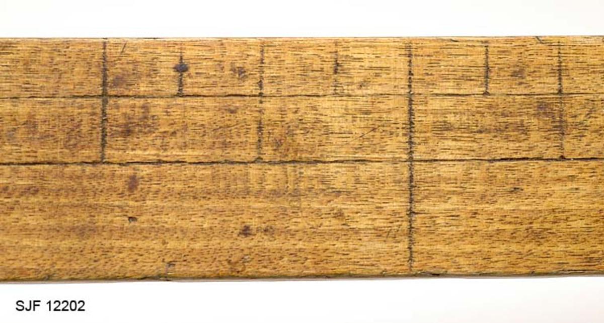 Klavelinjalen er tappet inn i den fremstae faste armen og festet med skruer. På den bevegelige armen er det under klavelinjalen festet et håndtak.  Sannsynligvis har klaven skala i tommer og centimeter. Det er risset inn merker i klavelinjalen som tyder på at det er tommer på den ene siden og centimeter på den andre.    Lengst bak på målelinjalen er det et hull for opphenging.  Klaven er trolig hjemmelaget.