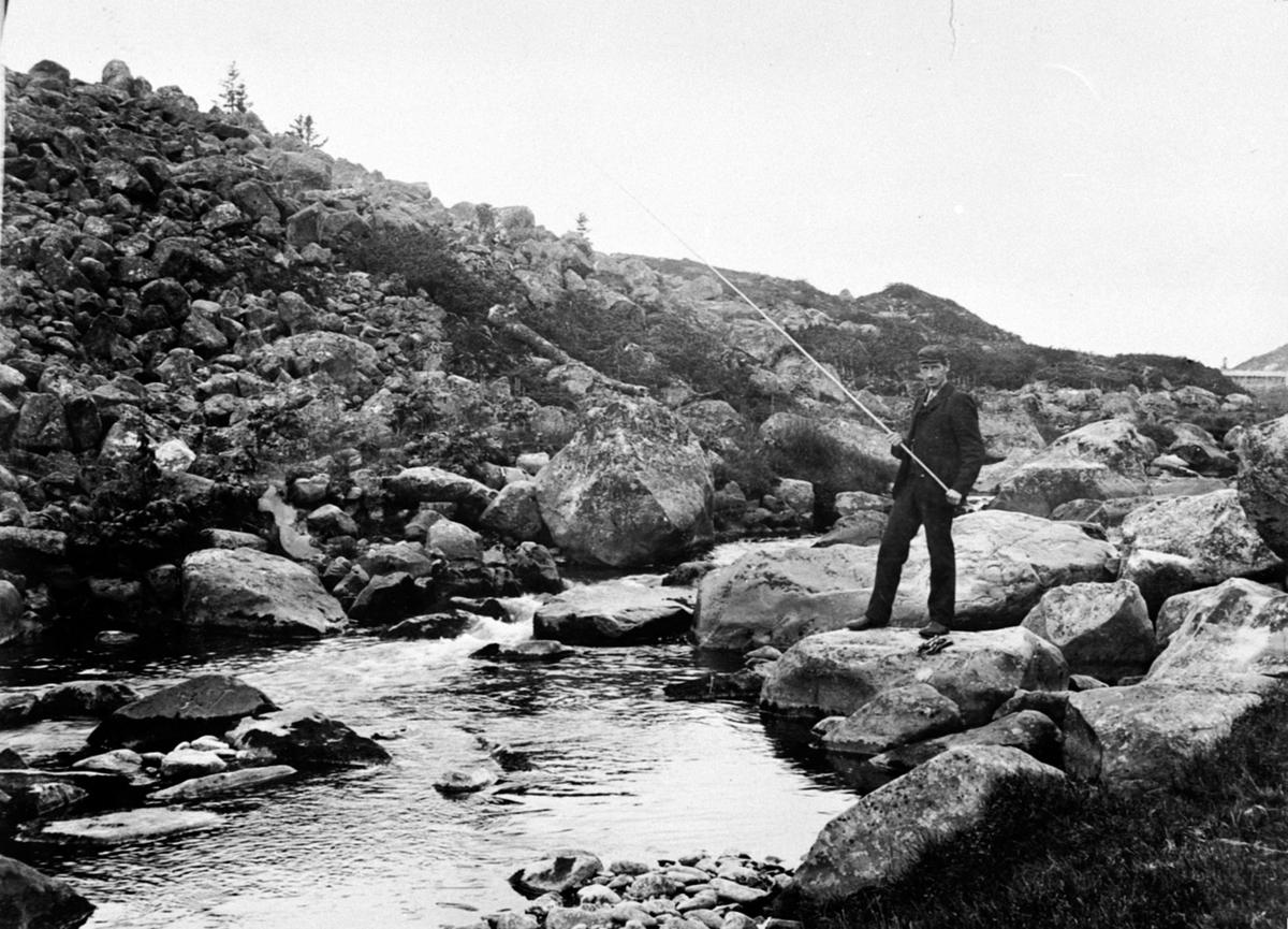 Mann fisker med markstang i Snultra, Ringsakerfjellet.