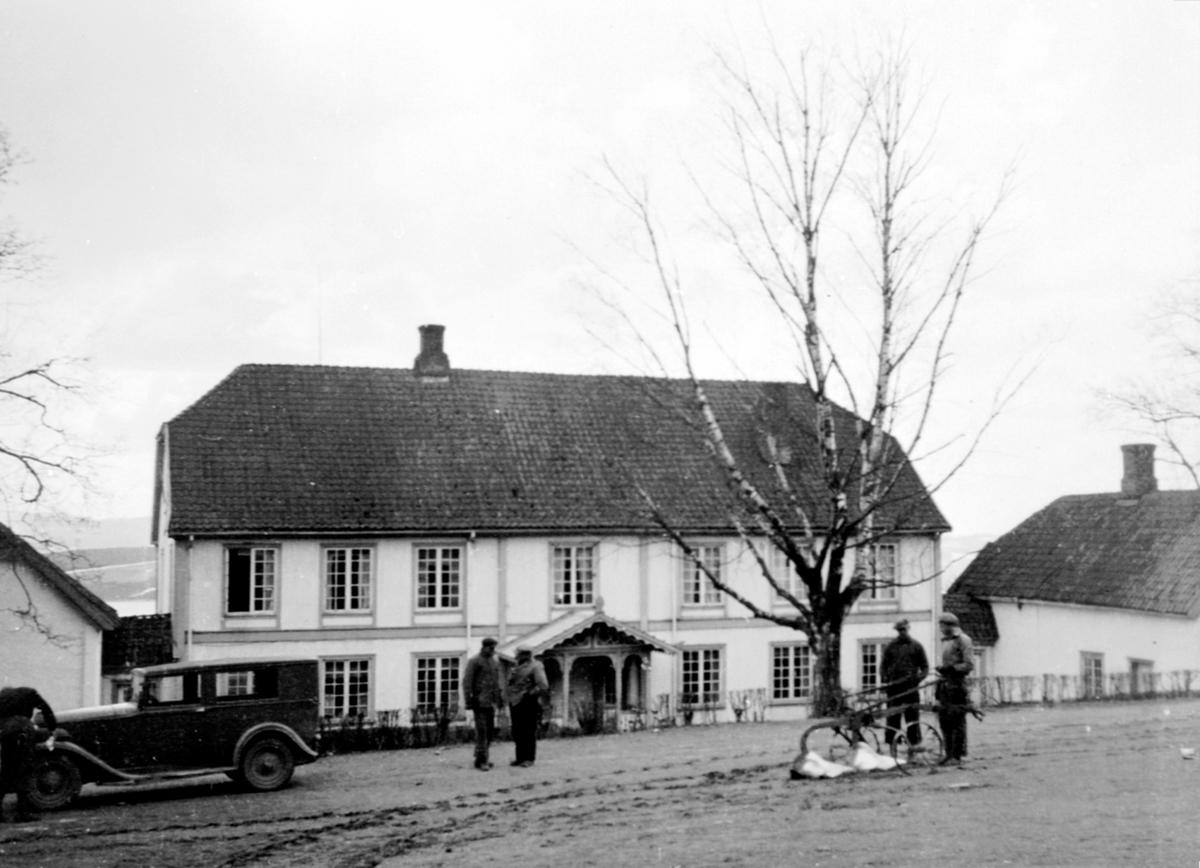 Hovedbygningen på Hovelsrud, Helgøya sett fra vegen. Bil og 5 karer i forgrunnen. Plog.