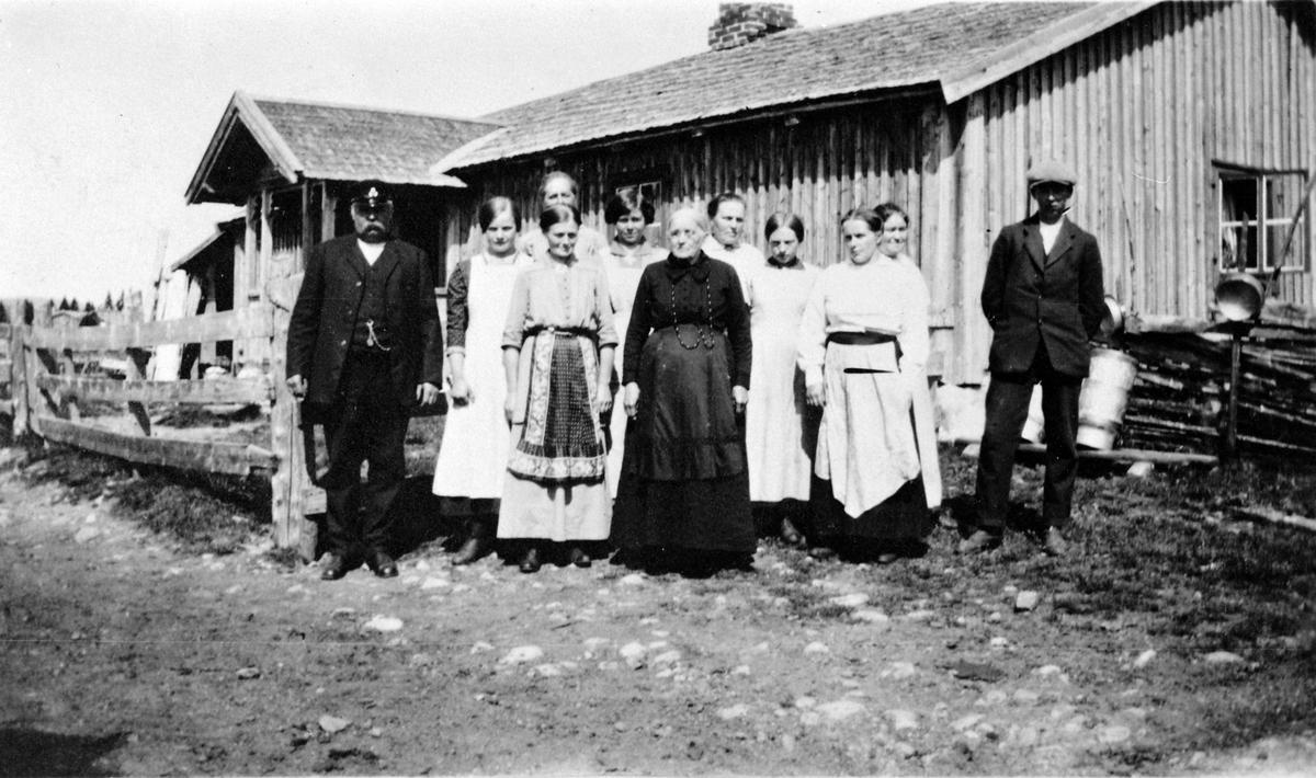 Gruppe personer utafor størhuset til Mørkved store på Nysætra. Til venstre er Thore Lien, dame i svart er Anne Lier, til venstre for henne er Oline Finstad, resten er ukjent. Ca. 1912.