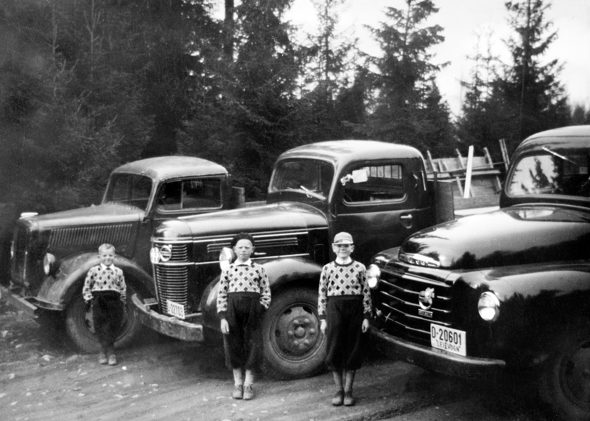LASTEBILER, EIER BJARNE STENSLI I NYBYGDA. Bilen til venstre er en ex tysk 3 tonn Opel Blitz. Som var den mest brukte lastebilen i den tyske hæren i andre verdenskrig, De to andre bilene er VOLVO D-22703, VOLVO D-20601, TRE GUTTER. Guttene er Bjørn, Kjell Ivar og Nils Petter Stensli. Sønnene til Bjarne Stensli.