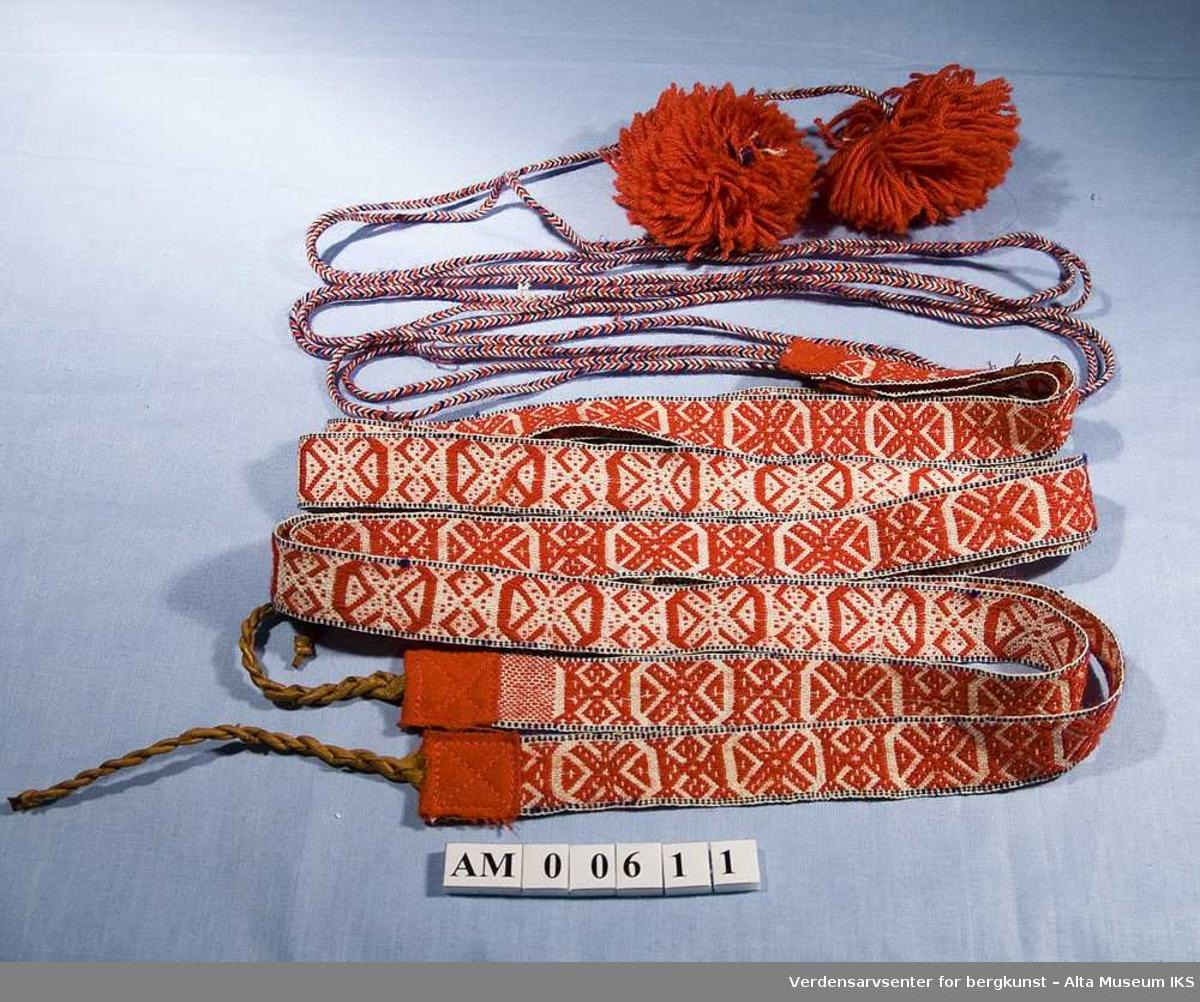 1 par grindvevde skallebånd. Endene er forsterket med rødt klede. Tvunnet skinnsnor for feste i skoen, L 15 cm. Flettet snor med dusk L 204 cm