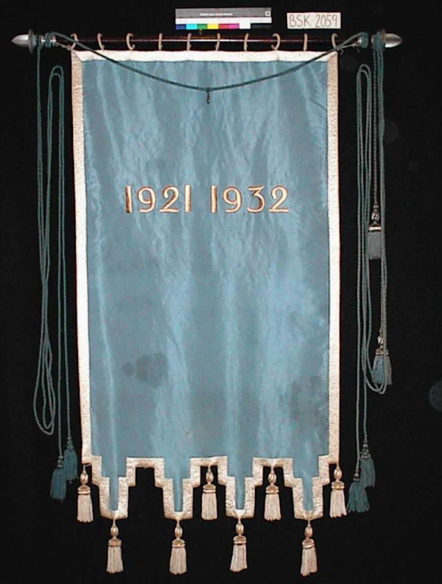 """Framside:  Tekst: """"NYGAARDS SKOLE"""" Motiv: Fakkel og to eikeløvkvister.  Bakside:  Tekst: """"1921   1932""""  4 cm bred brodert bord rundt hele fanen. Tynn snor helt ytterst. 8 dusker ved nedre kant. Uregelbunden nederkant."""