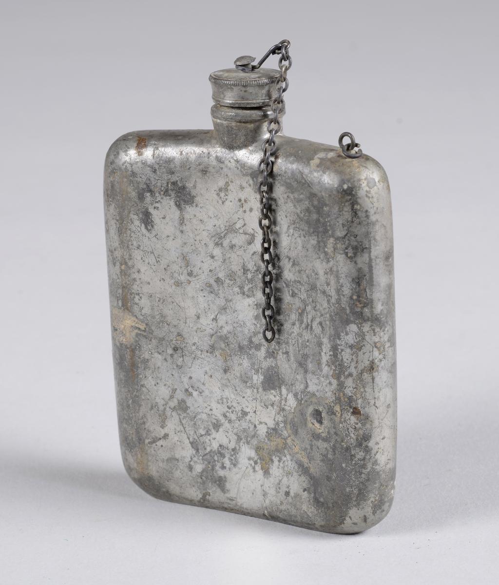 Flat rektangulær flaske av metall med rundede hjørner- og kanter. Lerka har rund skrukork som har vært festet til flasken med en kjetting. Kjettingen er nå kun festet til korken.