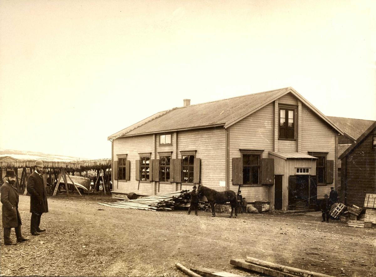 Esbensens butikk på Sletten i 1917. Hans Fredrik Esbensen med en annen mann i bildet. Fiskehjell i bakgrunnen.