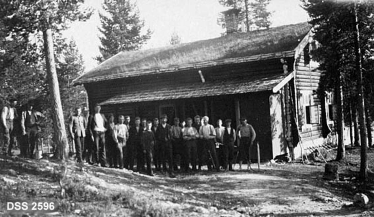 """Elevkull og lærere ved Kongsberg skogskole 1917-18 foran skogstua ved Sandorsæter, der skogskolens elever ble innkvartert i praksisperioder.  Gruppa er oppstilt foran et halvannenetasjes laftehus med stolpekonstruert veranda.  Torvtak på laftekjernen, flis på verandaen.  Bygningen er omgitt av barskog.   I skoleåret 1917-18 hadde Kongsberg skogskole 24 elever, og skogforvalter Eugene Münster (1878-1952) var hovedansvarlig for undervisningsaktivitetene, med den unge forstkandidaten Odd Cappelen (1891-1945) og en del andre ressurspersoner på Kongsberg som hjelpelærere.  Elevene fikk både praktisk og teoretisk opplæring.  Det var de praktiske øvelsene som preget den innledende delen av kurset.  Skoleåret startet tidlig i mai, med tømmerfløting, og fortsatte med planteskolearbeid og utplanting av barrotplanter i skogen.  Deretter fulgte krattrydding og vedhogst, myrgrøfting, takserings- og karteringsarbeid.  Den teoretiske undervisninga, som i tillegg til skogfaglige temaer omfattet matematikk, norsk, tysk og """"hygiene"""" (det som seinere ble kalt """"helselære"""").  Dette fotografiet er antakelig tatt i juli 1917, da elevene med skogstua på Sandoren som base drev med rydningshogst i ei granli ovenfor Buvatnet.  Undertrykt og skadd smågran ble felt og opphogd til lakterved, som det var stor etterspørsel under 1. verdenskrig, da tilgangen på annet brensel var vanskelig.  Veden ble påfølgende år fløtt på Kobberbergselva til Kongsberg.  I forbindelse med vedhogsten fikk elevene også en innføring i kuberingsarbeid."""