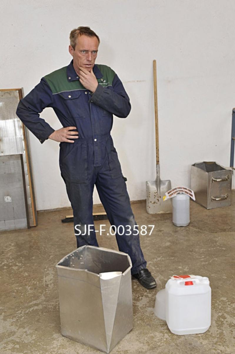 Frode Murud ved Skogfrøverket på Hamar, fotografert i frørenseriet.  Murud er kledd i arbeidsantrekk: En blå kjeledress med grønne skulderstykker.  Foran ham, på betonggolvet, står en forholdsvis diger aluminiumsbeholder med nyrenset granfrø.  Ved siden av denne beholderen står ei gråkvit plastkanne med rød skrukork.  Frøet skal helles over på denne kanna, før det legges på fryselager i påvente av at Skogfrøet får en bestilling fra nettopp dette frøpartiet.  Velrenset skogfrø med høy spireprosent er kostbar vare.  For å unngå spill bruker Murud ei diger plasttrakt, som vi skimter bak kanna på golvet.
