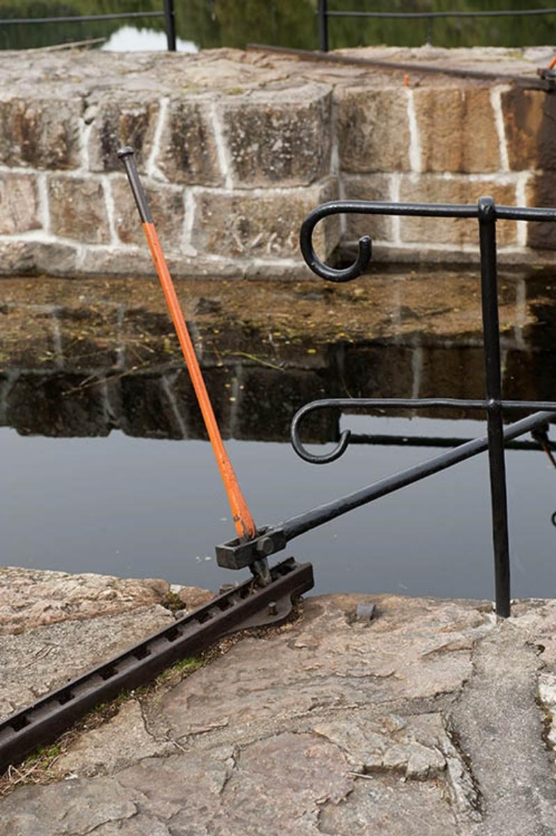 Innløpet til øvre sluseport i Lunde sluse i Bandak-Norsjø-kanalen.  Fotografiet er tatt fra søndre kanalbredd, hvor vi ser hvordan portene var stengt ved hjelp av smijernstenger og oransjefarget nylontau.  I forgrunnen den perforerte jernskinna som ble brukt når slisdeporten skulle «spettes» opp eller igjen. Lunde sluse har ett slusekammer og en løftehøyde på tre meter.