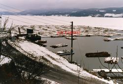 """Utilslagsplassen ved Aslaksborg i Gvarv i Telemark, fotografert vinteren 1986.  Fotografiet er tatt fra bakkeskråningen ovenfor vegen der tømmerbilene kjørte inn og ut av plassen.  Til venstre i bildet skimter vi ei «vogge», ei ramme som tømmeret fra bilene ble lastet over i ved hjelp av bilenes kraner.  Så ble det slått vaierbindsel rundt virket, før stakene på vassdragssida ble slått ned og vogga ble bikket mot skråningen som førte ned mot Norsjø ved hjelp av en hydraulisk innretning.  Tømmerbuntene ble liggende og flyte i et innlenset område utenfor.  Da dette fotografiet ble tatt var Norsjø islagt, med unntak av det innlensete området, som ble holdt åpent ved hjelp av strømdannere.  Norsjø var ofte islagt, og dermed ikke fløtbar, i februar, mars og begynnelsen av april. Ved siden av den nevnte vogga ser vi også et lite hus med pulttak.  Dette var et overbygg over motoren til hydrauliske anlegget for """"voggene""""."""