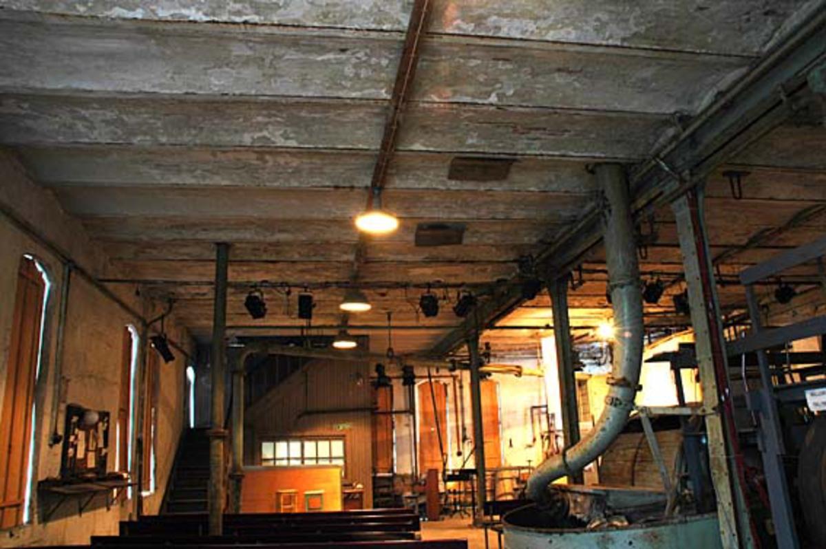 Interiør fra hollenderiet ved Klevfos Cellolose- & Papirfabrik i Løten i Hedmark.  Dette anlegget har siden 1986 vært drevet som Klevfos industrimuseum.  I den salen der dette fotografiet er tatt ble råstoffene til papiret oppløst, blandet, malt og forvandlet til masse, som kunne kjøres på papirmaskinen i en tilstøtende del av bygningen.  Rommet fikk navn etter den maskinen vi skimter overdelen av til høyre i forgrunnen -  «hollenderen».  Dette var et maleapparat i et digert støpejernstrau med tilførselsrør fra det ovenforliggende limloftet.  I trauet eller karet finnes en roterende valse, der ytterflata er besatt med kniver som maler massen mot et «grunnverk», som er utstyrt med samme type kniver.  Spalta mellom kubben og grunnverket kunne justeres for å oppnå ønsket malingsgrad.  Poenget var å oppnå ei masse der fibrene filtret, limte og klistret seg sammen slik at papiret fikk gode styrkeegenskaper.  Hollenderne på Klevfos sto i en sal der etasjeskillene under og over var utført som sjølbærende kappehvelv mellom stålskinner.  Langs midten av rommet var konstruksjonen forsterket ved hjelp av klinkenaglete søyler, som bar en horisontal ståldrager under kappehvelvene.  På dette fotografiet skimtes også noen kroker i taket, som ble brukt når det skulle heises på plass industrielt utstyr, med tau og taljer.  I forbindelse med 100-årsjubilett for Klevos Cellulose- & Papirfabrik i 1988 ble det skrevet og framført et teaterstykke, «Arbesdaer», med temaer fra livet i og omkring fabrikken.  For å få vist dette stykket ble hollenderiet delvis ombygd til teatersal, med sittebenker for publikum og med en liten scene ved trappene og formannskontoret innerst i lokalet  Ettersom forestillingen har vist 5-6 ganger hver sommer siden primieren, har benkene, scenen og litt teaterlys blitt en del av det faste inventaret.  Også lemmene foran de høye, støpejerninnfattete vinduene i teglsteinsveggen til venstre er montert med sikte på å kunne ha et noenlunde kontrollerbart teaterlys i d