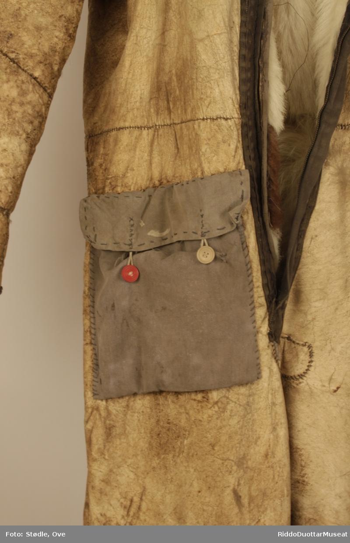 Hel dress, 173 lang. Sydd av saueskinn og sannsynligvis storfeskinn, med hårsiden innover.  Kragen er sydd av saueskinn med ullsiden ut. Glidelås-lukning. Ligner en gammel flydress. Lomme øverst på høyre lår er sydd av grått stoff, og har en rød og en brun knapp.