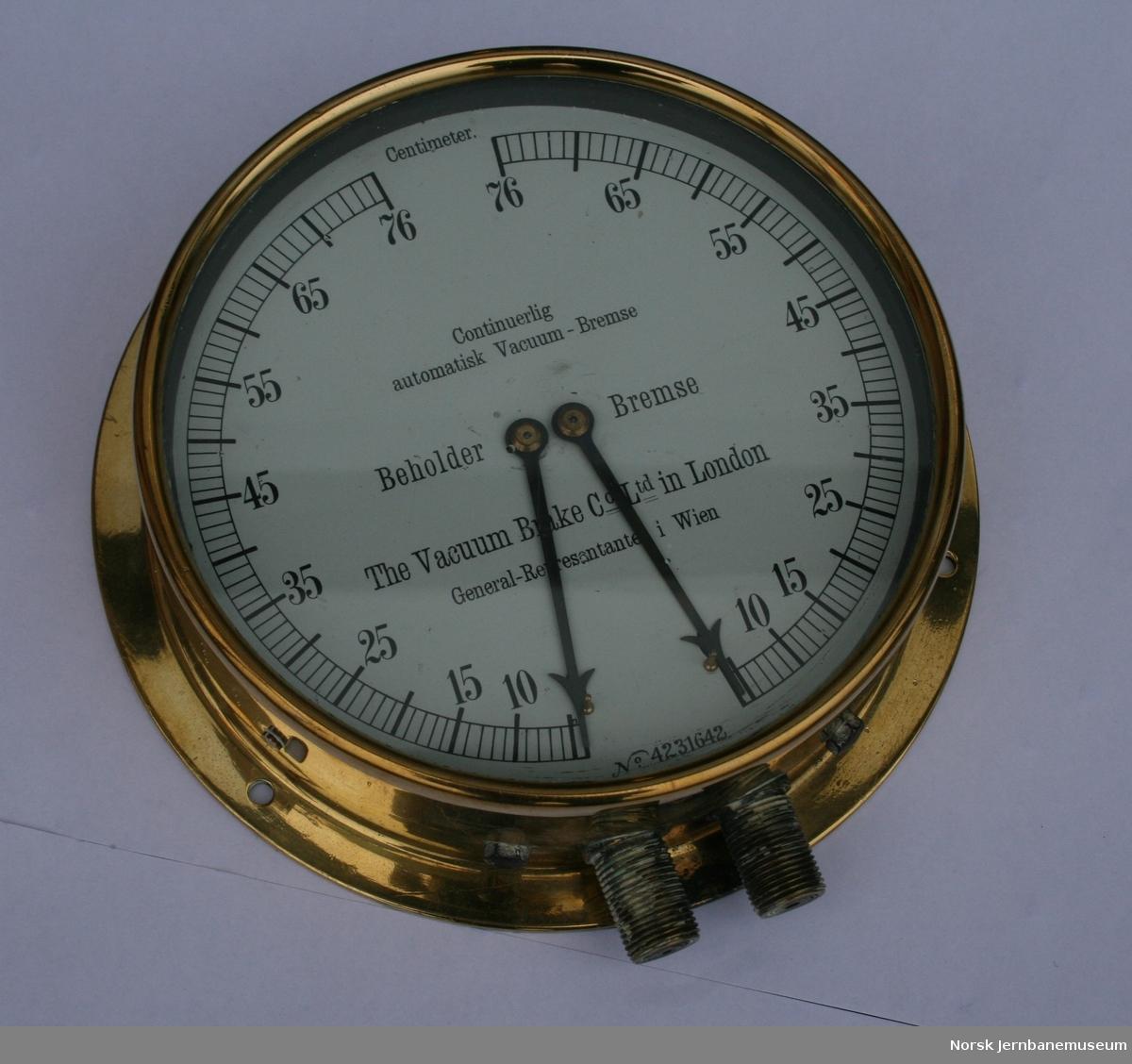 Dobbelt manometer/ vakuummeter (2 visere, en for vakuumbeholder og en for bremseledning). Viser vakuum målt i cm kvikksølvhøyde. 76 cm kvikksølvhøyde tilsvarer 1 atmosfære.