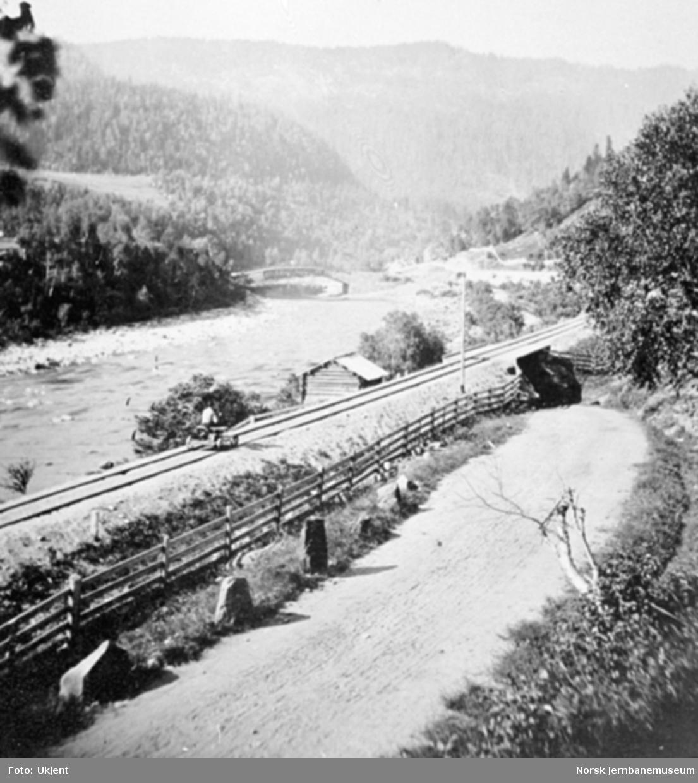 Jernbanelinjen med landevegen ned Fjeset-bakken, en vegundergang og Osøy bru i bakgrunnen