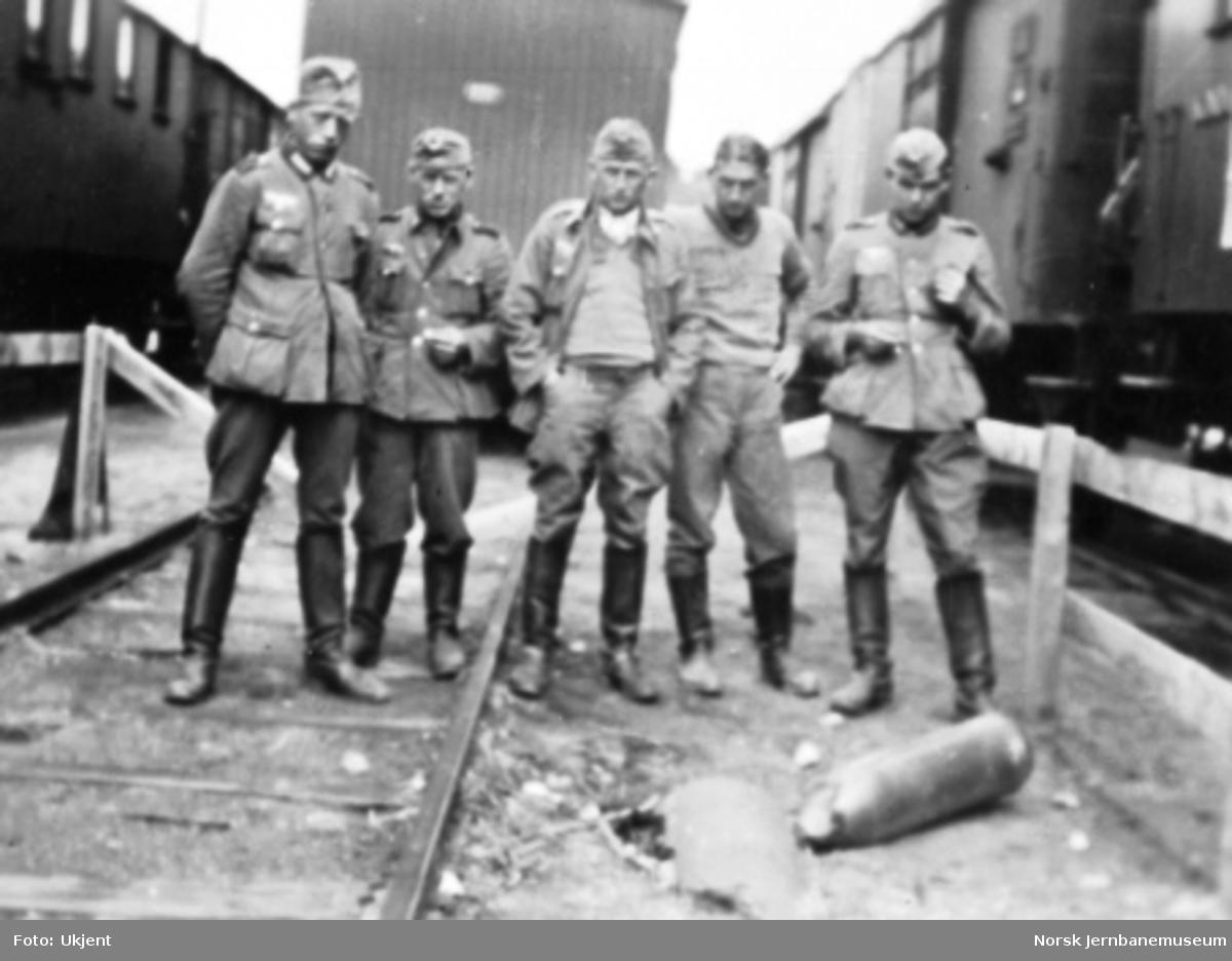 Dombås stasjon etter bombingen i april 1940; soldater ser på en udetonert bombe
