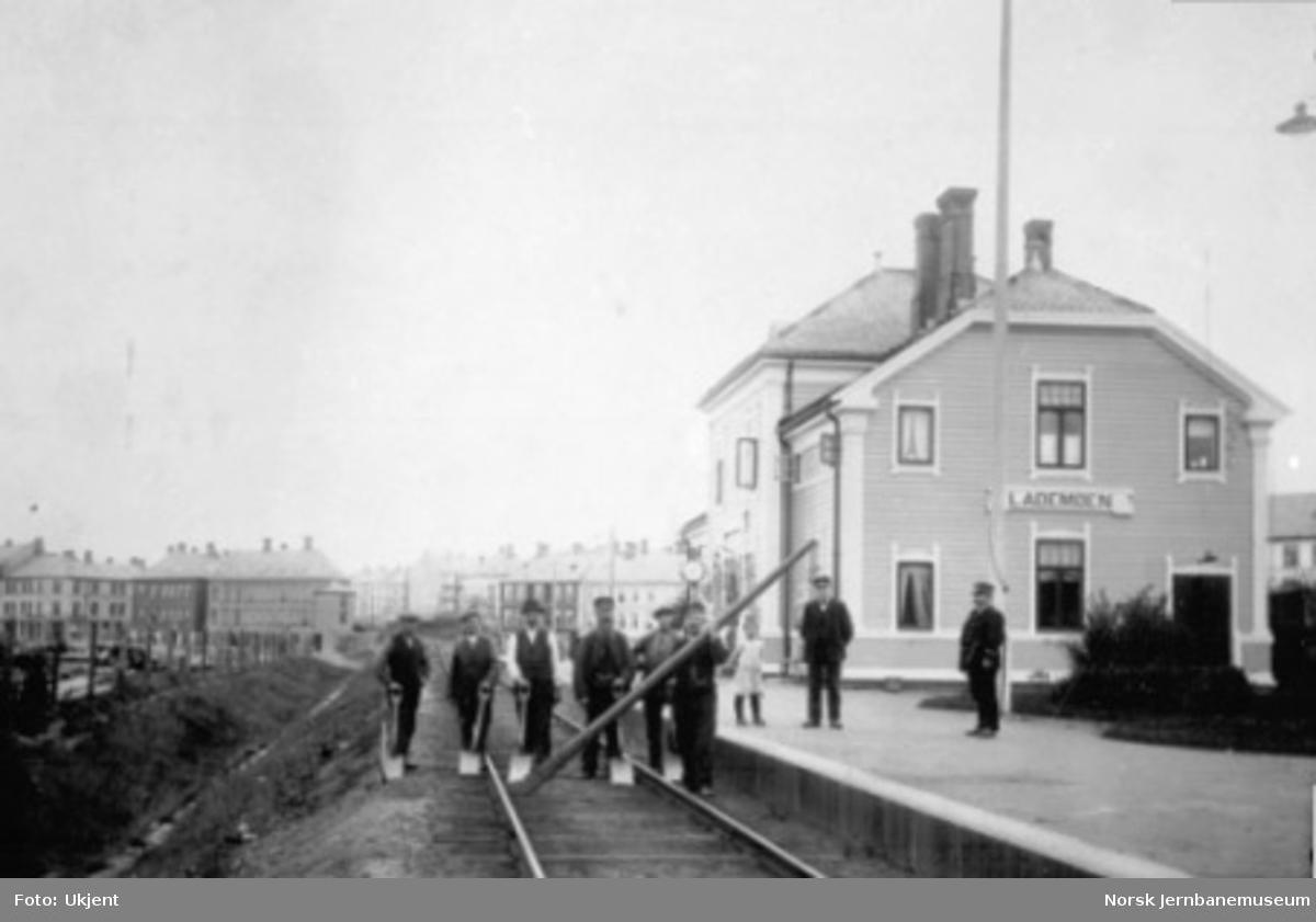 Banearbeidere med spader og en stolpe i sporet og stasjonspersonale på plattformen foran ekspedisjonsbygningen på Lademoen