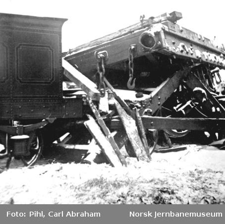 Lillestrøm-godstoget trukket av lok nr. 7 har kjørt inn i steinbufferen på Oslo Ø, vi ser bakre del av tenderen på lokomotivet og en ødelagt tømmervogn