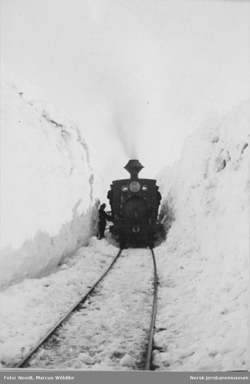 Damplokomotiv type VI mellom høye brøytekanter på Arvedalslinjen (Kongens Grubes bane) pæl 600, sett i retning Rugldalen
