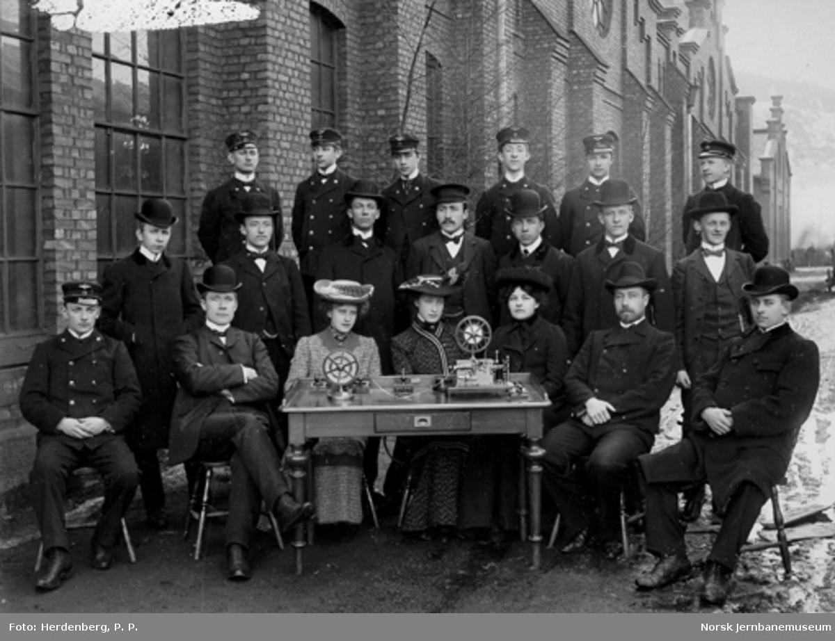 Gruppebilde med 20 telegrafistelever bak et bord med telegrafiapparater