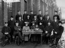 Gruppebilde med 20 telegrafistelever bak et bord med telegra
