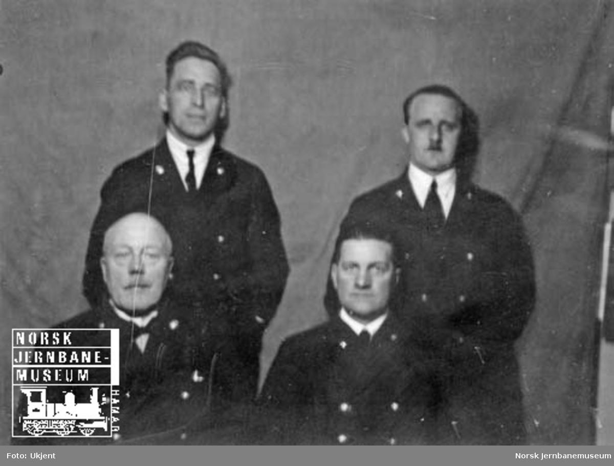 Gruppebilde av fire jernbanemenn på Hamar stasjon, trolig godsekspedisjonen