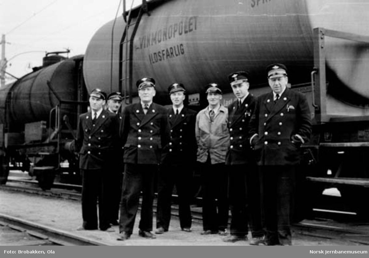 Gruppebilde av sju jernbanemenn på Hamar stasjon foran en sprit-tankvogn