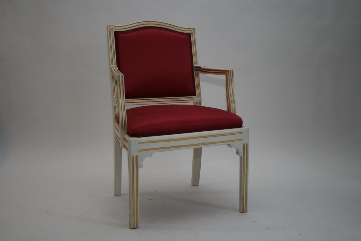 En av to stoler, m. armlener. Empire, hvite med gull, rødt silketrekk. Profilerte hjørneklosser.